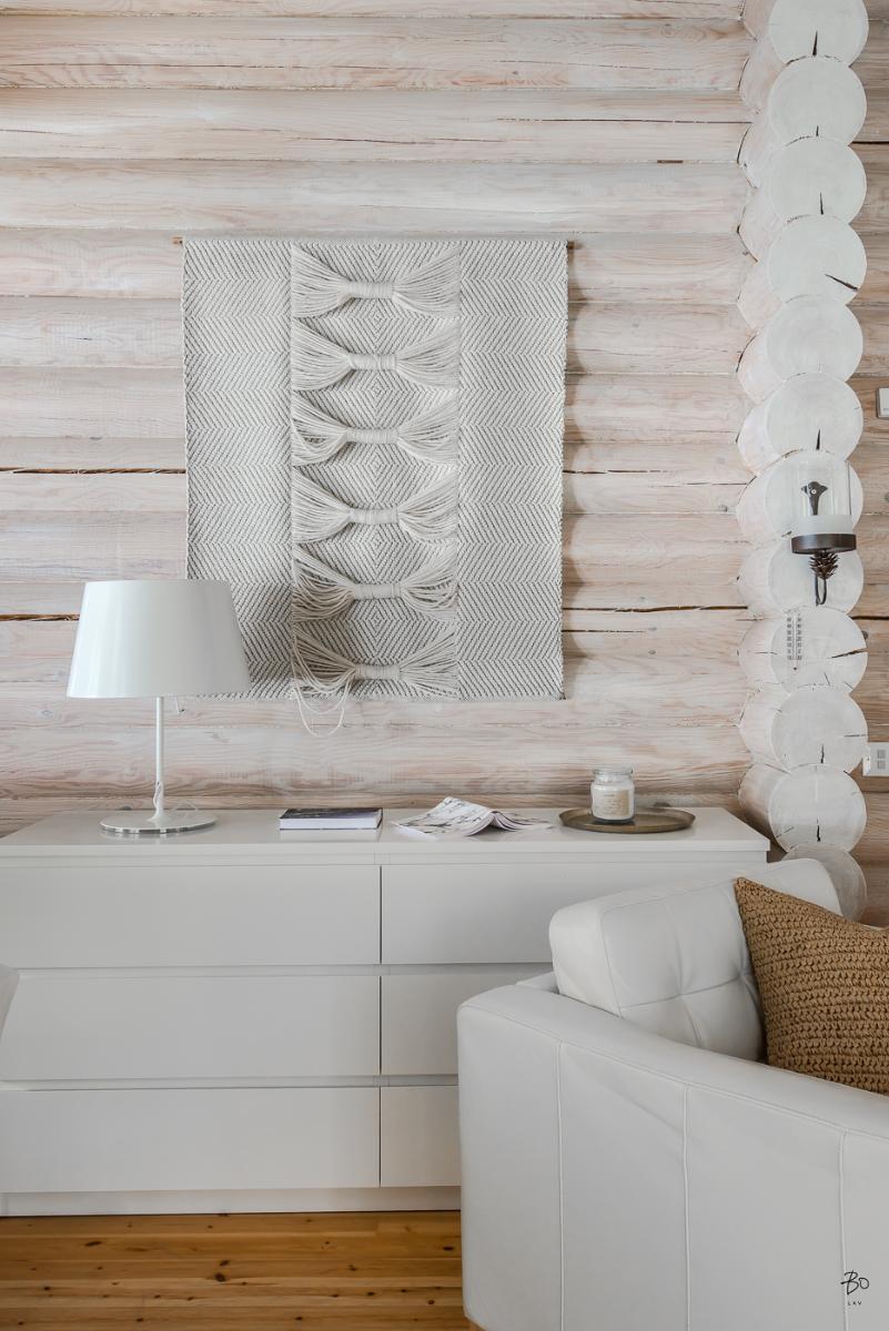 Tapisserie sur mur en rondins de bois blanchis