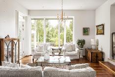 Olohuone tulvii valoa lattiaan ulottuvien ikkunoiden ansiosta.