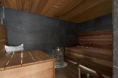 Modernissa saunassa myös silmä lepää - seinissä Tulikiven mustaa luonnonkivilaattaa.