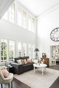Koko olohuoneen seinä on täynnä ikkunoita ja on hyvin valoisa.