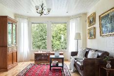 Korkea erkkeri-ikkuna kruunaa tilavan olohuoneen.