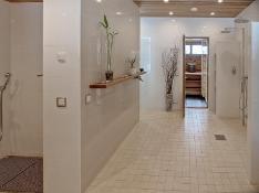 Saunan tilava pesuhuone, jonka yhteydessä höyrysauna, erillinen kuraeteinen ja wc.