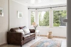 Takkahuoneen iso erkkeri-ikkuna tuo runsaasti valoa ja idyllisen pihamaiseman sisään.
