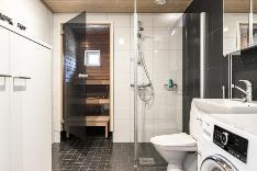 Pesuhuone on tilava, jossa on hyvin tilaa pesutornille, pyyhkeille ja likapyykeille.