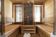 Sun Saunan ylellinen löylyhuone on tilava ja korkeat ikkunat luovat tasapainoisen ilmeen.