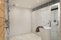 Saunan yhteydessä olevassa pesuhuoneessa vaaleaa Carrara -marmorimosaiikkia ja 2 sadesuihkua.