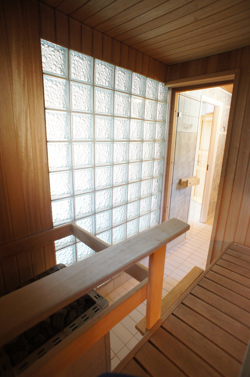 Sauna lasitiiliseinällä ja ikkunalla title=