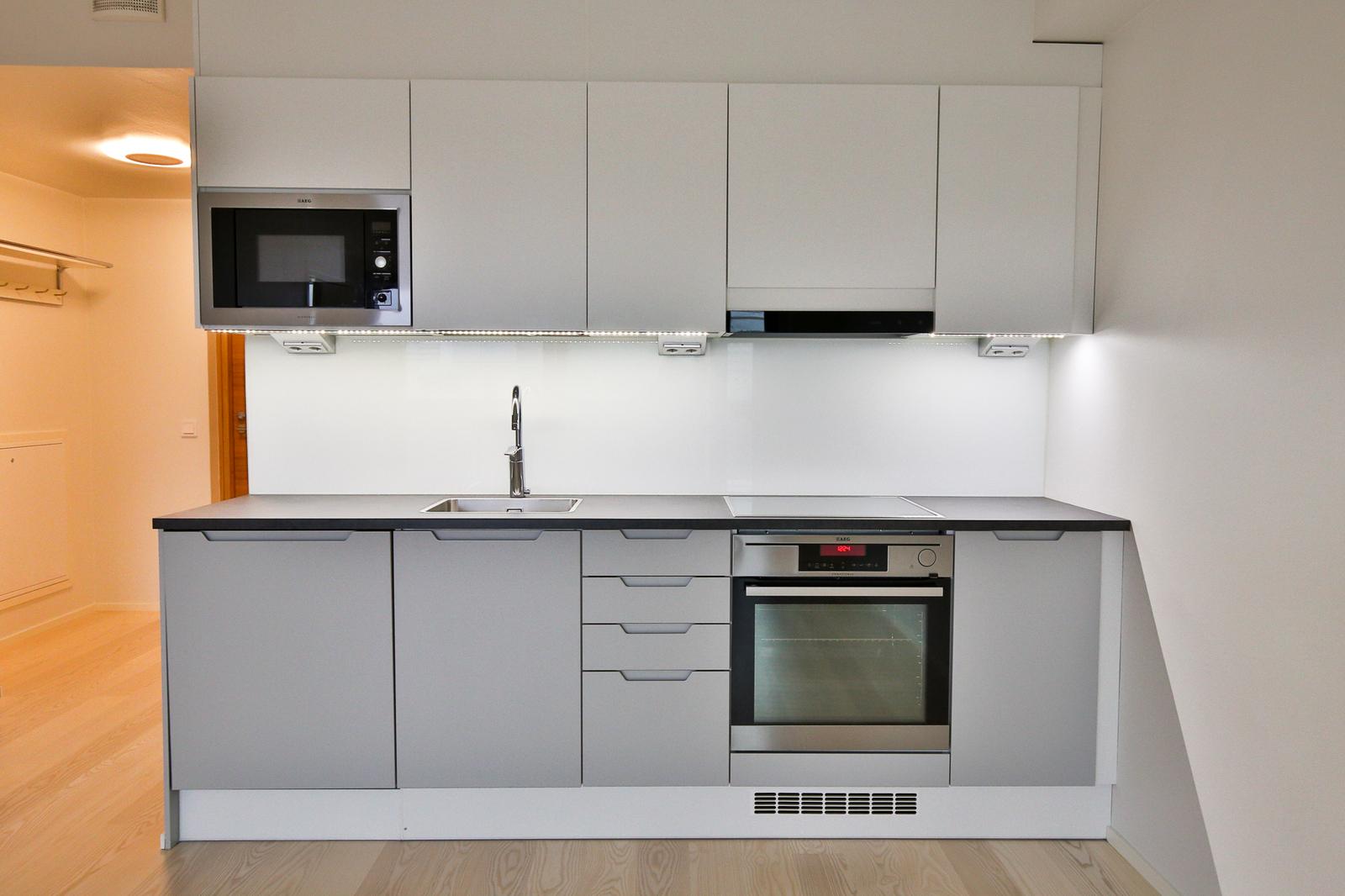 A La Carte- keittiö on tyylikkään harmaa- valkoinen ja varustettu laadukkain AEG- kodinkonein. title=