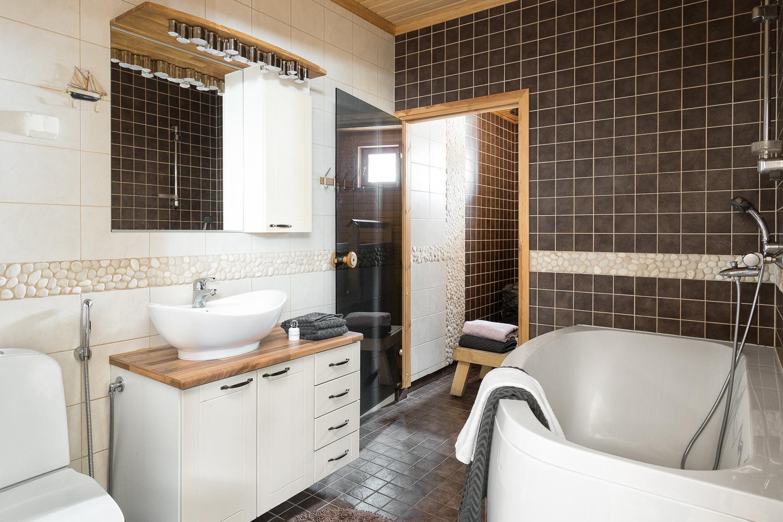 Saunaosaston pesutilassa on amme ja luonnonkivitehostelaatoitusta. title=