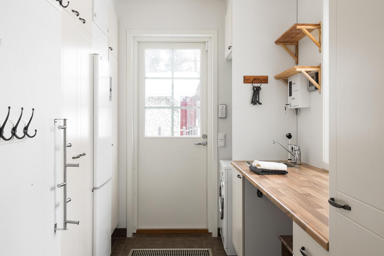 Toimivassa kodinhoitohuoneessa on erillinen sisäänkäynti kurastopperilla. title=