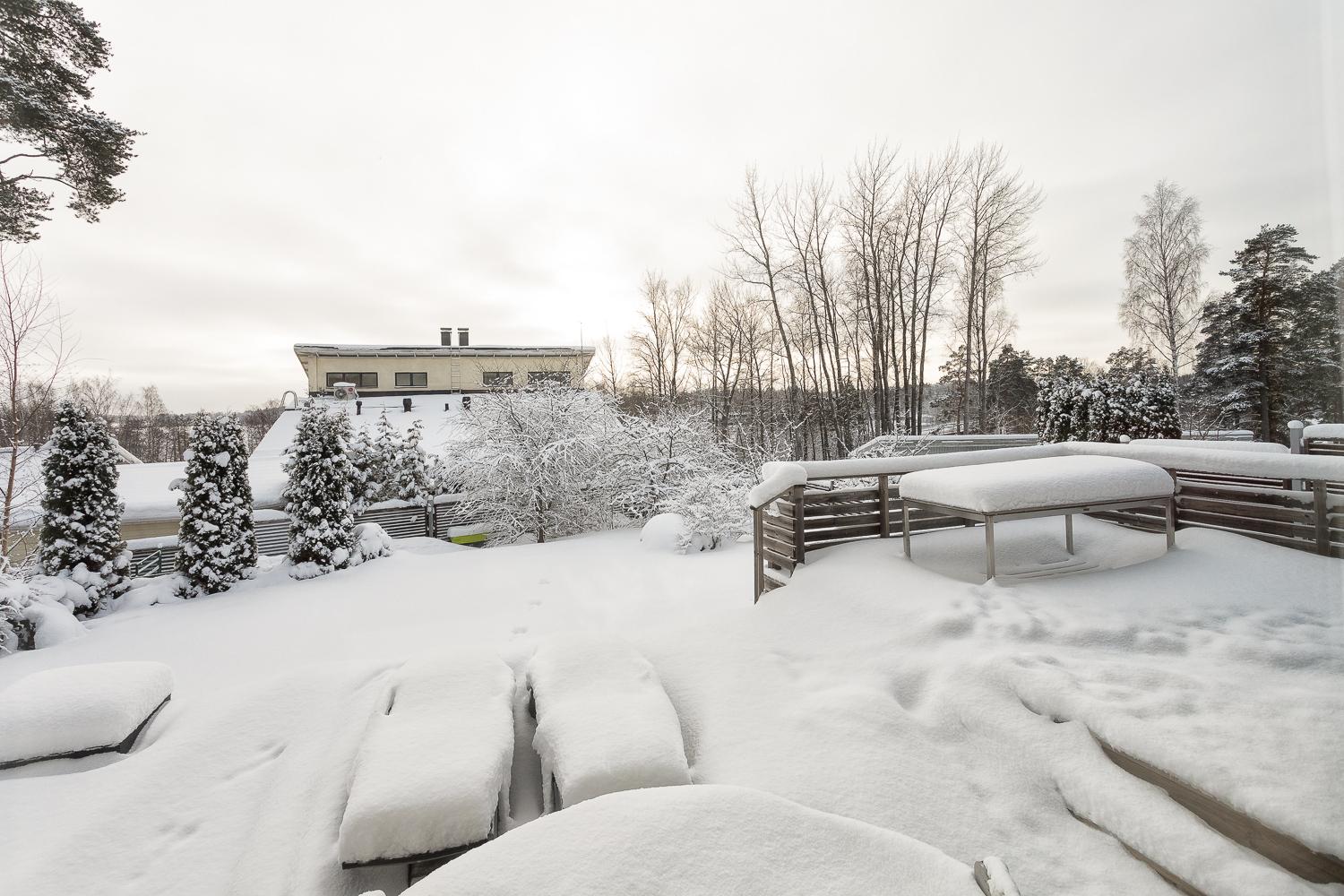 Etelään avautuva terassi ja puutarhapiha on vaipunut lumipeitteen alle talvehtimaan. title=