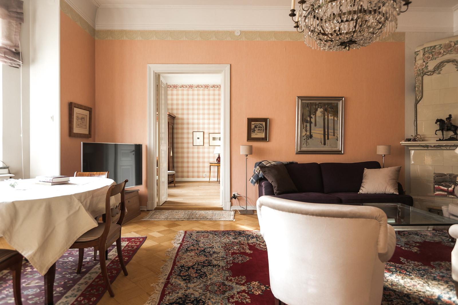 Ison olohuoneen kruunaa kaunis kaakeliuuni, joita asunnossa on kolme kappaletta. title=