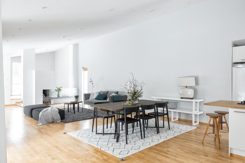 Ruokailutila ja olohuone ovat yhtenäistä tilaa, vino sisäkatto lisää tilan avaruutta. title=
