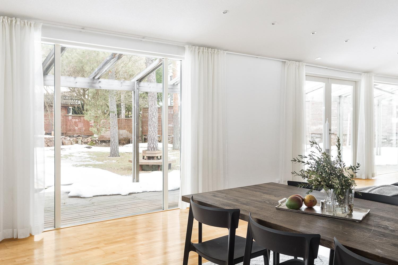 Kookkaat lattiaan asti ulottuvat ikkunat saavat tilan kylpemään valossa title=