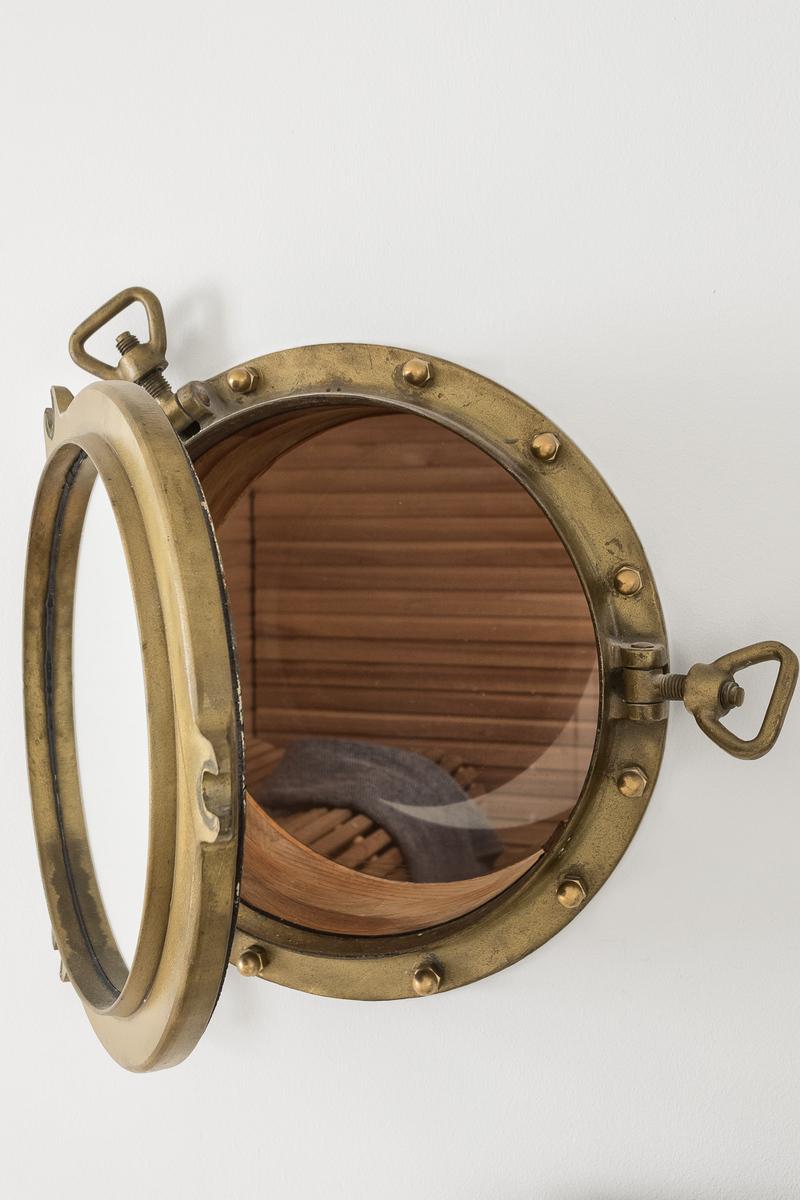 Yksilöllinen ja aito messinkinen laivanikkuna avautuu saunaan. title=