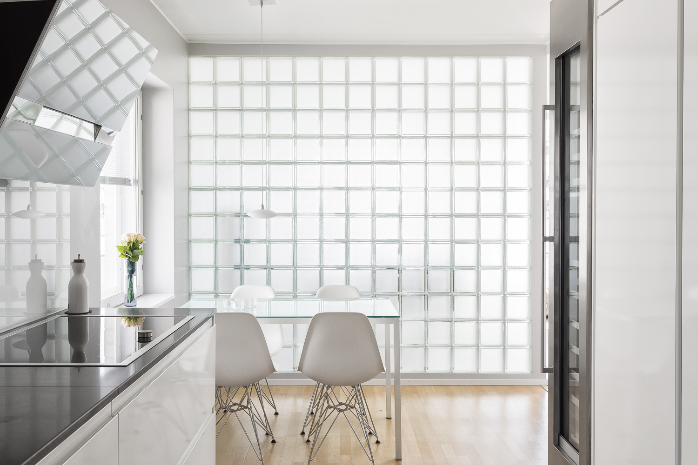 Keittiön ja ruokailutilan välissä valoa tuova lasitiiliseinä. title=
