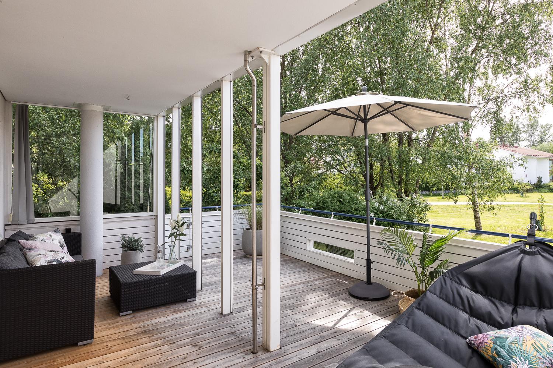 Iso osittain katettu terassipiha toimii kesällä olohuoneena.  title=