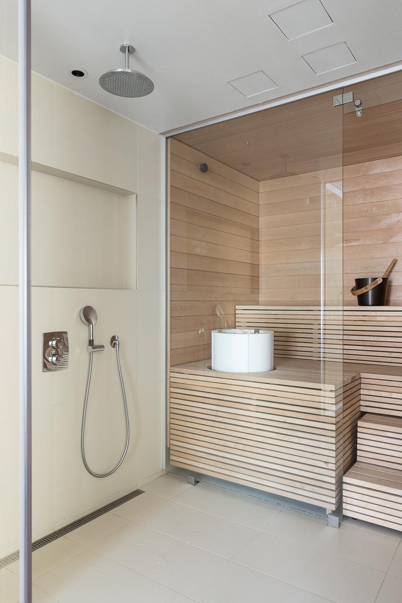 Moderni valoisa sauna pesutiloineen. title=