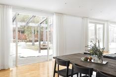 Kookkaat lattiaan asti ulottuvat ikkunat saavat tilan kylpemään valossa