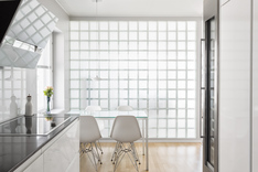 Keittiön ja ruokailutilan välissä valoa tuova lasitiiliseinä.