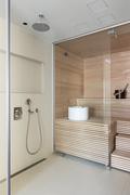 Moderni valoisa sauna pesutiloineen.