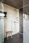 Rantasaunan kylpyhuone on korkeatasoinen varusteiltaan ja materiaaleiltaan.