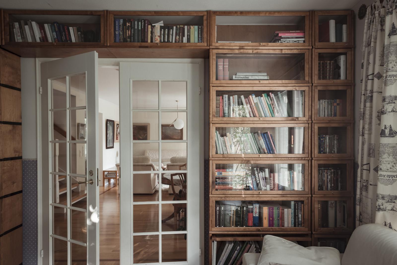 Kirjaston hyllyihin mahtuu luettavaa. Pariovet johtavat olohuoneeseen. title=