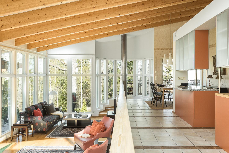 Olohuone yhdistyy kaarevien portaiden kautta ruokailutilaan ja keittiöön. title=
