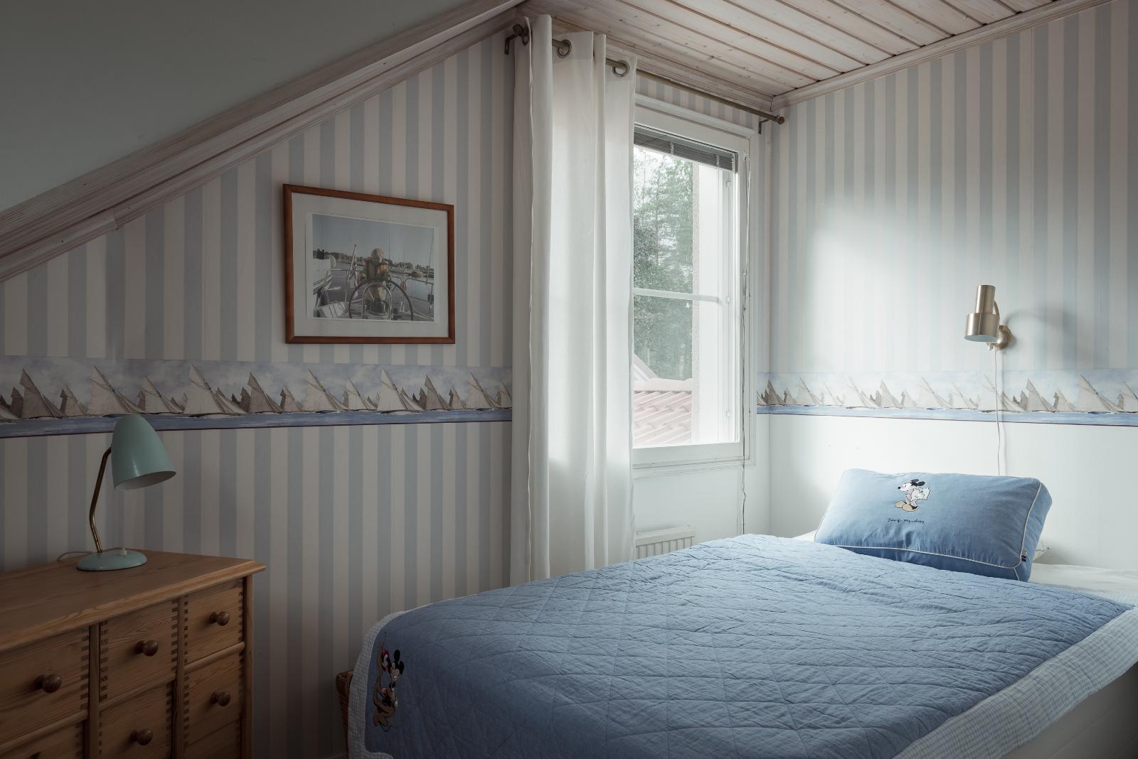 Makuuhuoneiden vinot sisäkatot tuovat huvilamaista tunnelmaa. title=