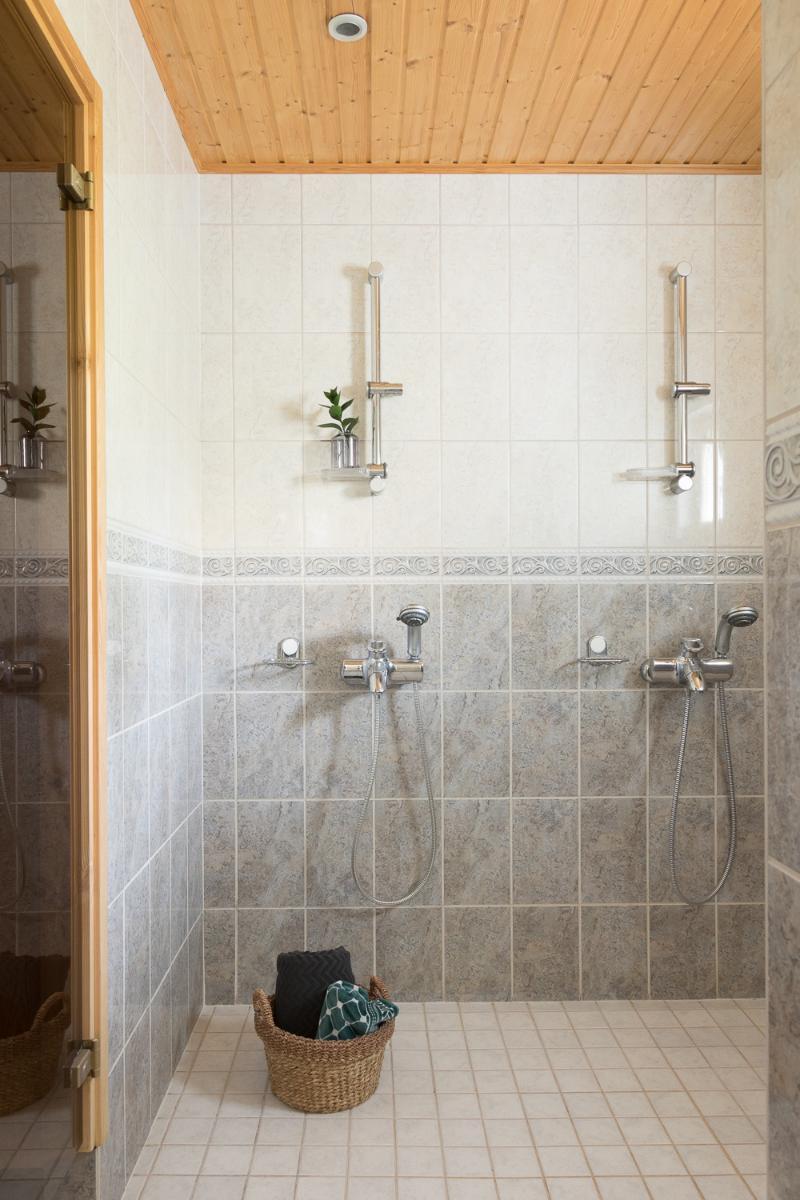 Ajattoman harmaa-valkoinen pesuhuone 2:lla suihkulla. title=