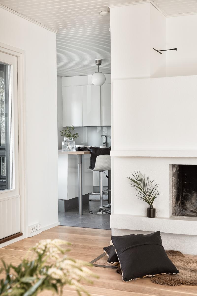 Näkymää olohuoneesta keittiöön. Olohuoneessa on muurattu takka.  title=