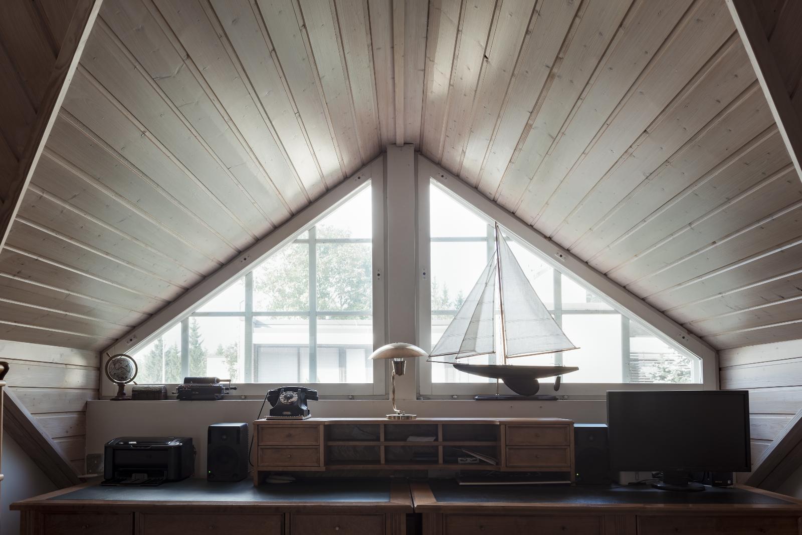 Yläkerran sisäkaton näyttävä harja ja suuret yläikkunat tuovat arkkitehtonisuutta ja ilmeikkyyttä. title=
