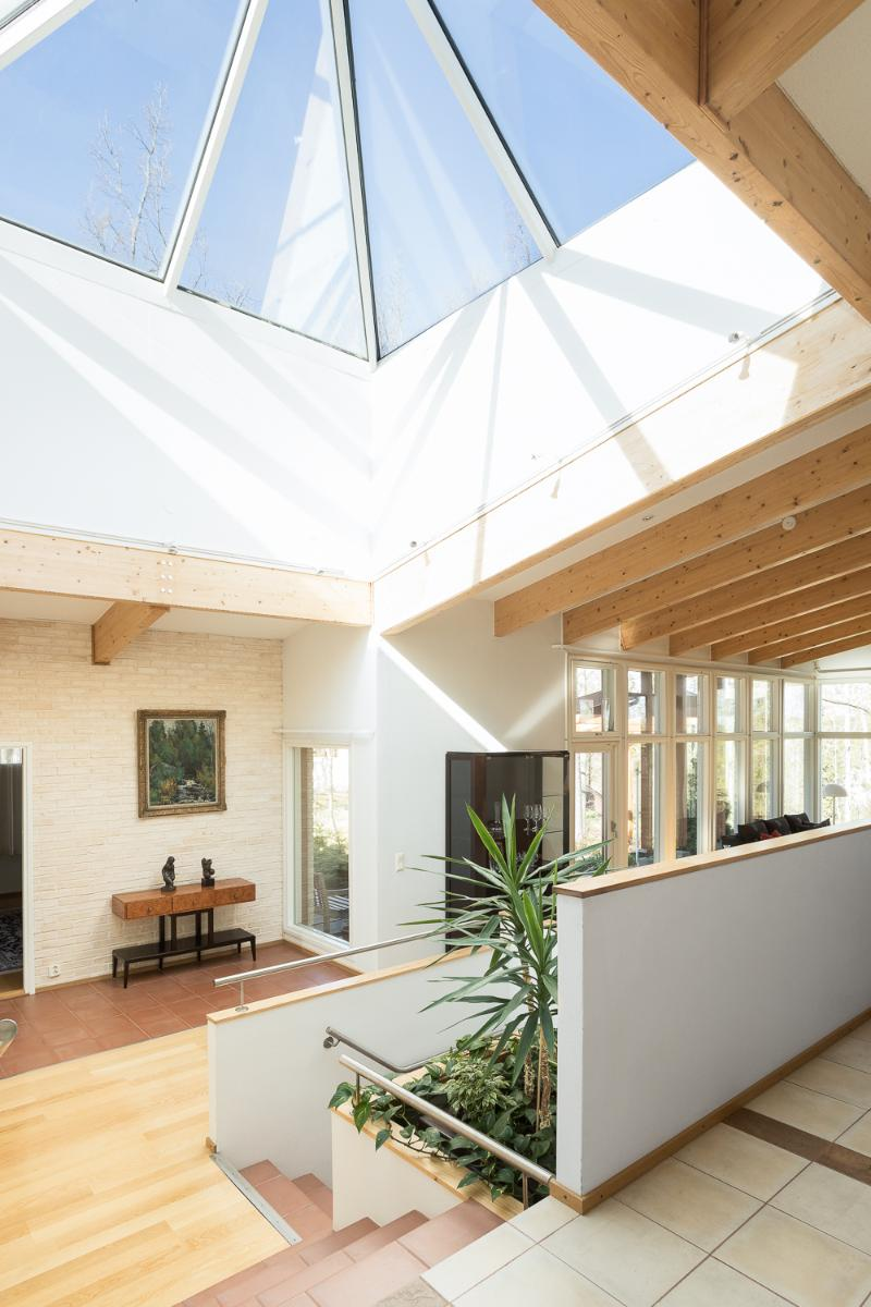 Aulan kookas kartionmuotoinen kattoikkuna tuo runsaasti valoa avaraan tilaan. title=