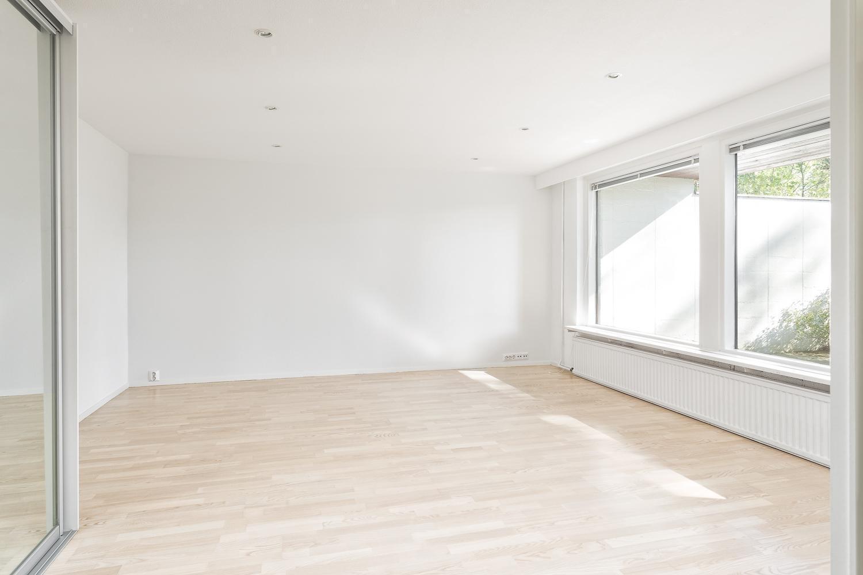 Alakerran tilava makuuhuone suurilla ikkunoilla title=