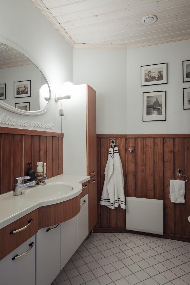Osassa kylpyhuoneista ja wc:istä on käytetty seinäpanelointia tuomaan lämmintä tunnelmaa. title=
