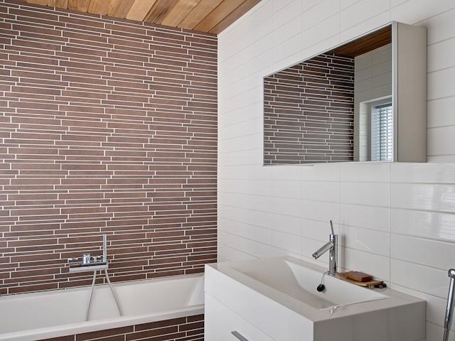 Yläkerran makuuhuoneen yhteydessä ammeellinen kylpyhuone. title=