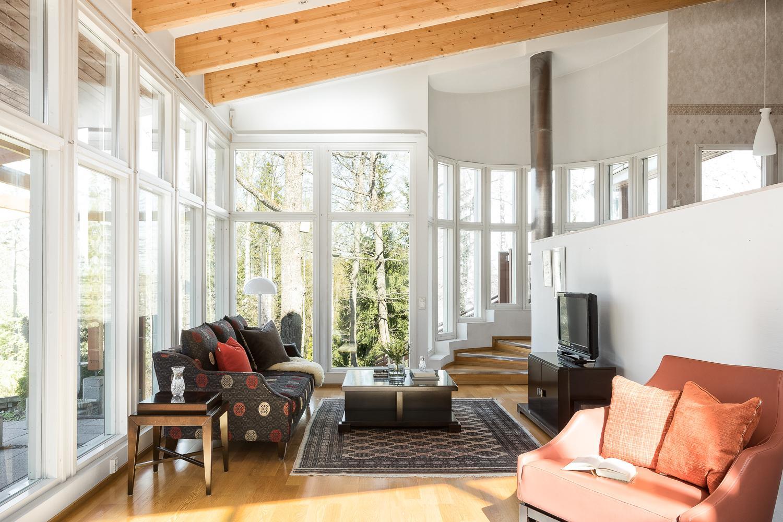 Olohuone runsaine lattiaan ulottuvine ikkunoineen. title=