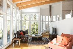 Olohuone runsaine lattiaan ulottuvine ikkunoineen.