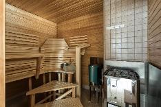 Sauna jossa sähkö- ja puukiuas sekä muotolauteet.