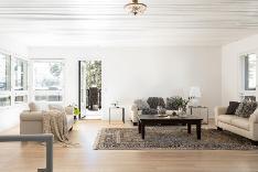 Valoisa olohuone, jossa ikkunat kolmeen eri ilmansuuntaan.