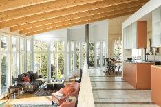 Olohuone yhdistyy kaarevien portaiden kautta ruokailutilaan ja keittiöön.